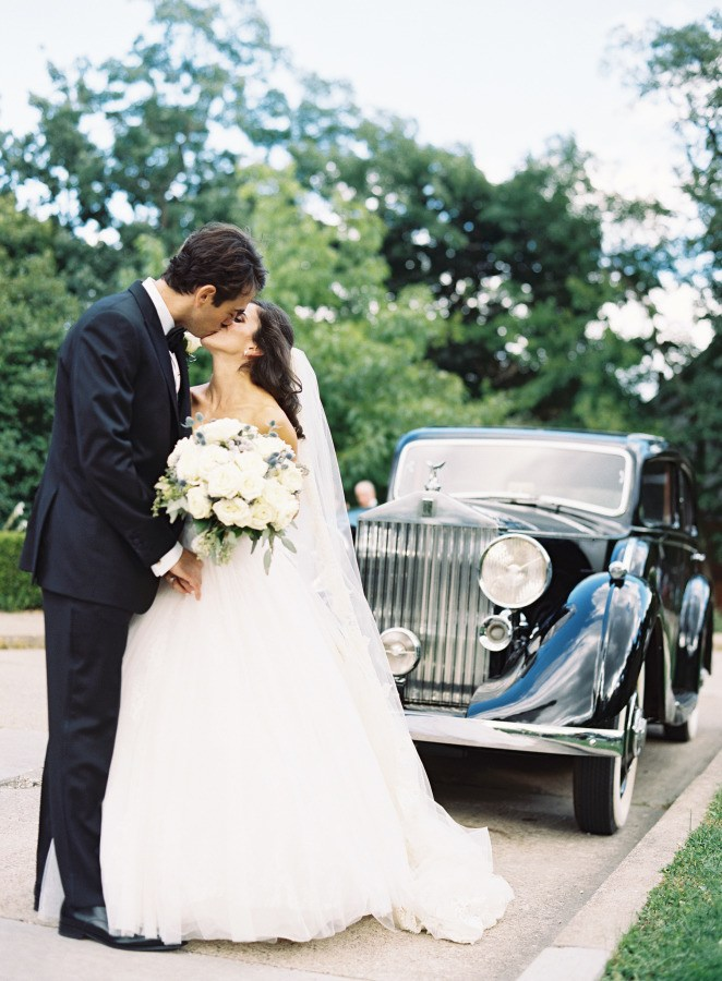 Bride and groom in front of a car