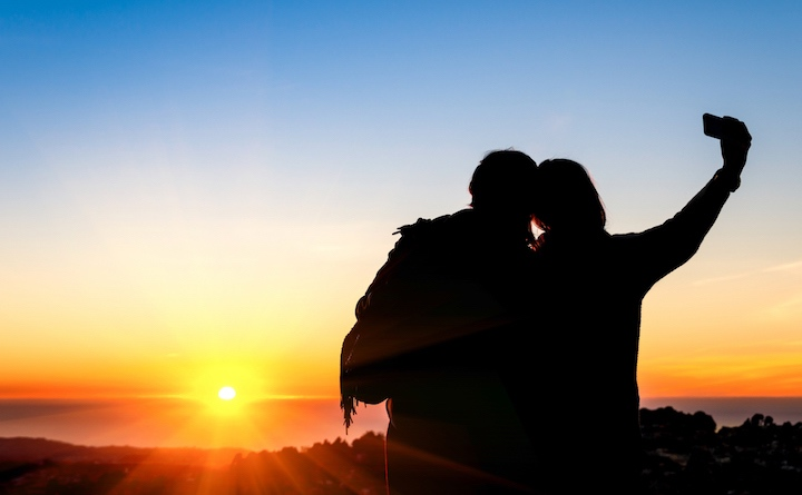 Couple of best friends taking selfie during sunset at Twin Peaks in San Francisco - Modern concept of friendship with new trends and technology - Travel girlfriends having emotional fun together
